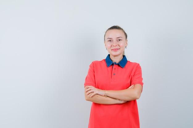 Jonge vrouw met gekruiste armen in t-shirt en vrolijk kijken