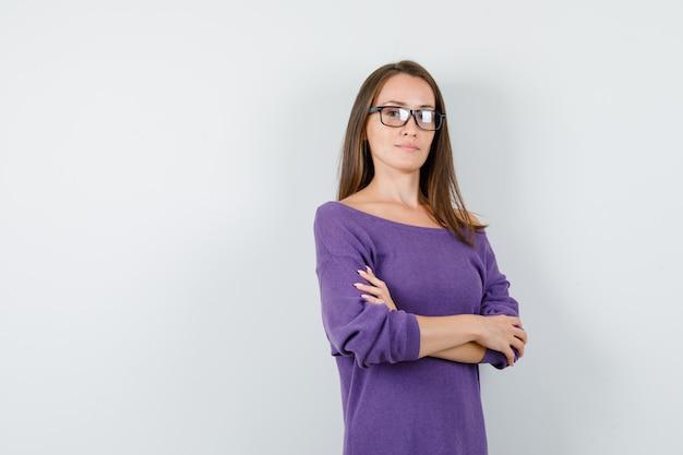 Jonge vrouw met gekruiste armen in violet overhemd en op zoek zelfverzekerd. vooraanzicht.