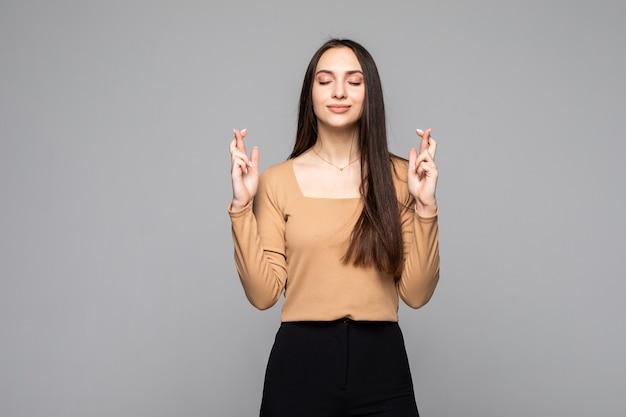 Jonge vrouw met gekruiste vingers geïsoleerd op een grijze muur