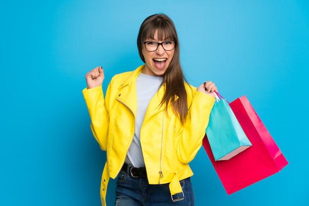 Jonge vrouw met gele jas op blauw met veel boodschappentassen in overwinning positie