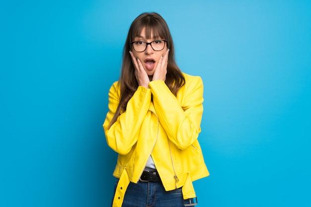 Jonge vrouw met gele jas op blauwe achtergrond verrast en geschokt tijdens het kijken naar rechts