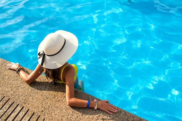 Jonge vrouw met gele strooien hoed rusten in zwembad met helder blauw water op zonnige zomerdag