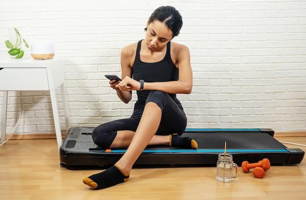 Jonge vrouw met gemengd ras maatregelen activiteitscontrole met smartphone