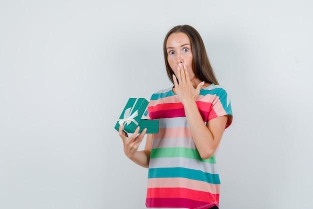 Jonge vrouw met geopende geschenkdoos in t-shirt en op zoek verbaasd. vooraanzicht.
