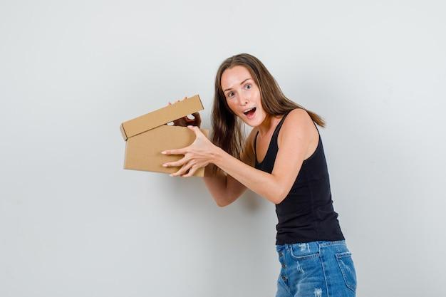 Jonge vrouw met geopende kartonnen doos in hemd, korte broek en op zoek opgewonden.