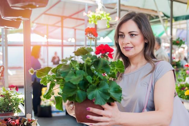 Jonge vrouw met geranium in kleipot bij tuincentrum. tuinieren, planten - vrouw met geranium bloemen