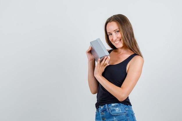 Jonge vrouw met geschenkdoos in hemd, korte broek en op zoek blij. vooraanzicht.