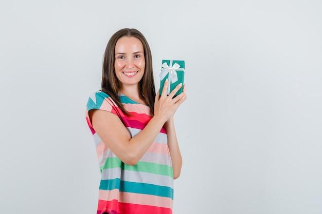 Jonge vrouw met geschenkdoos in t-shirt en op zoek gelukkig. vooraanzicht. Gratis Foto