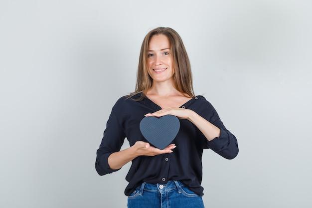 Jonge vrouw met geschenkdoos in zwart shirt, jeans broek en op zoek vrolijk