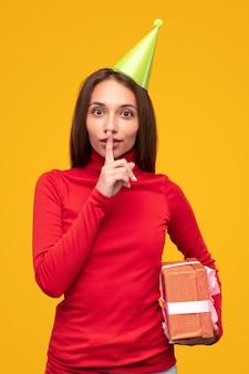 Jonge vrouw met geschenkdoos stilte gebaar maken en vragen om geheim te houden tijdens verjaardagsviering