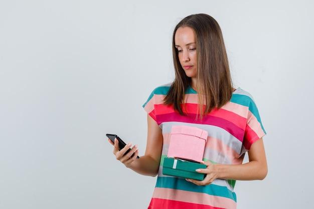 Jonge vrouw met geschenkdozen en kijken naar telefoon in t-shirt vooraanzicht. Gratis Foto