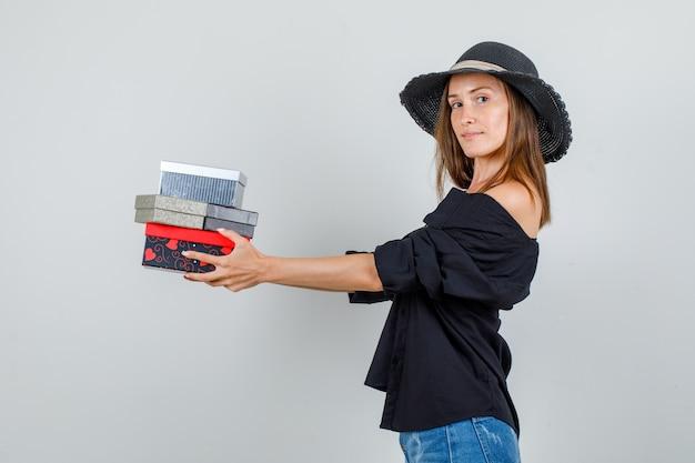 Jonge vrouw met geschenkdozen en lachend in shirt, korte broek, hoed.