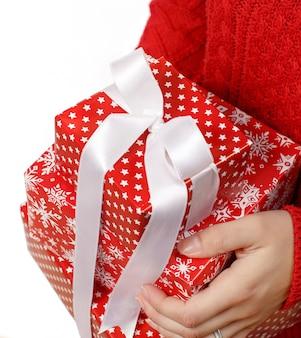Jonge vrouw met geschenkdozen in handen geïsoleerd op wit close-up
