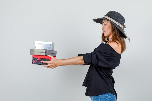 Jonge vrouw met geschenkdozen in shirt, korte broek, hoed en op zoek naar ernstig.