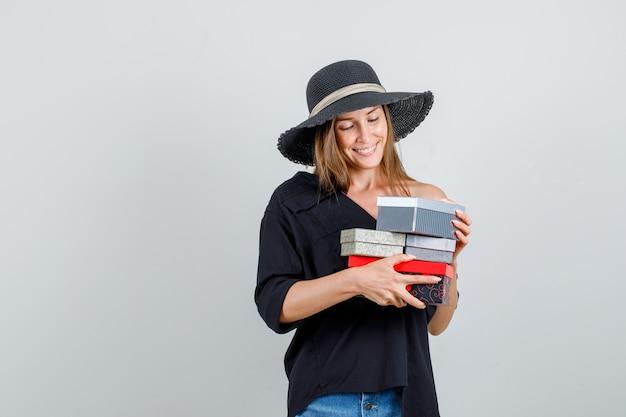 Jonge vrouw met geschenkdozen in shirt, korte broek, hoed en op zoek vrolijk