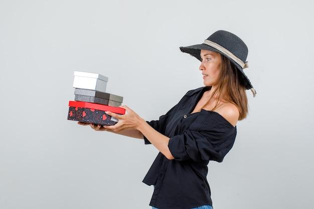 Jonge vrouw met geschenkdozen in shirt, korte broek, hoed en voorzichtig kijken.