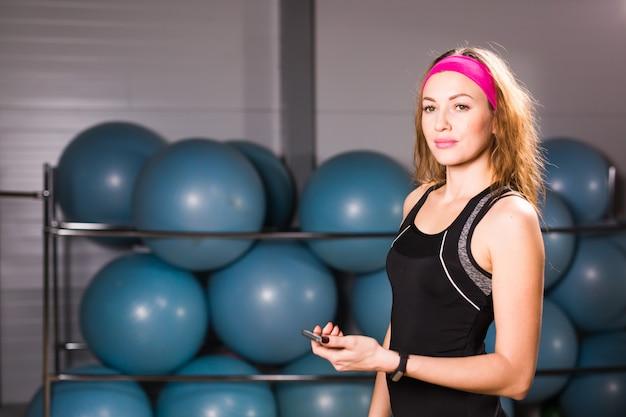 Jonge vrouw met geschiktheidsdrijver en smartphone in gymnastiek