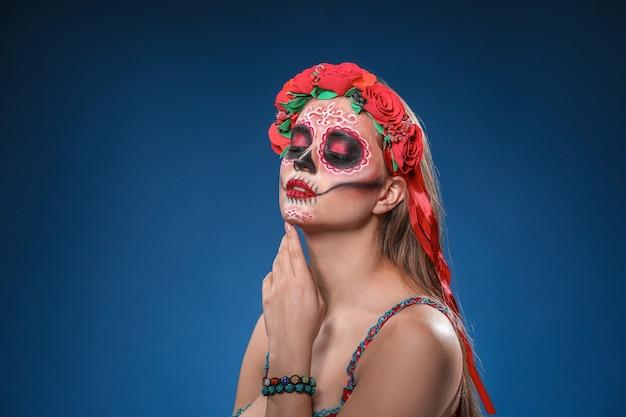 Jonge vrouw met geschilderde schedel op haar gezicht voor mexico's dag van de doden tegen kleur