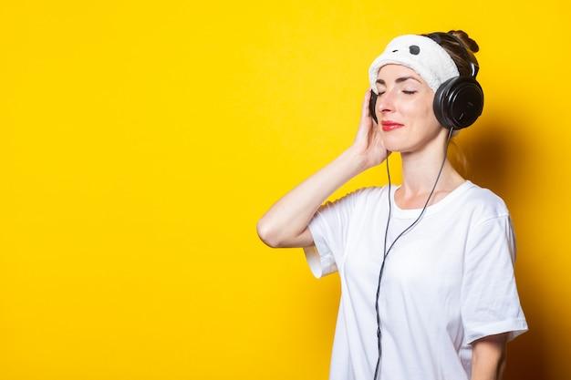 Jonge vrouw met gesloten in slaapmasker en in hoofdtelefoons die aan muziek luisteren