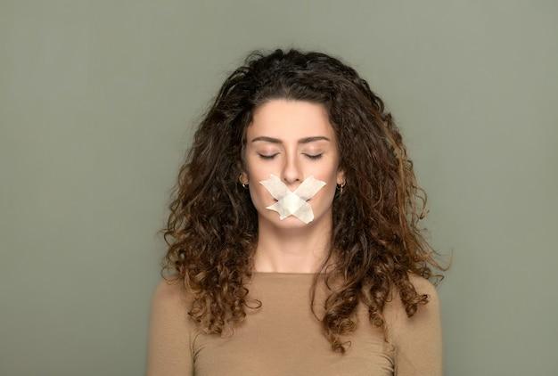 Jonge vrouw met gesloten ogen en haar mond dichtgeplakt in een concept van censuur van visie en vrije meningsuiting over een grijze studioachtergrond