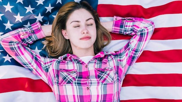 Jonge vrouw met gesloten ogen het liggen op de vlag van de vs