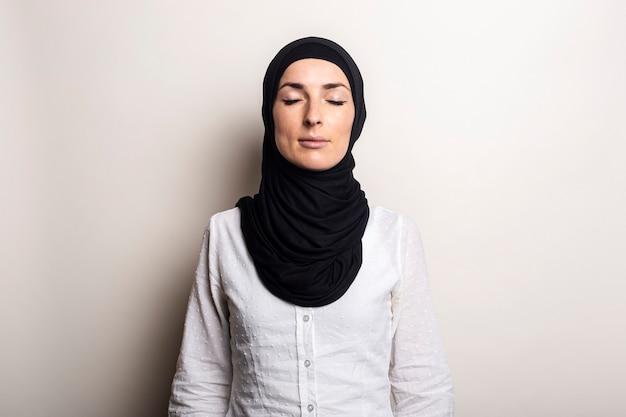 Jonge vrouw met gesloten ogen in wit overhemd en hijab