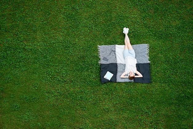 Jonge vrouw met gesloten ogen liggend op de deken op groen gras
