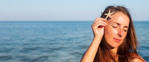 Jonge vrouw met gesloten ogen met een zeester op de achtergrond van de zee. banier.