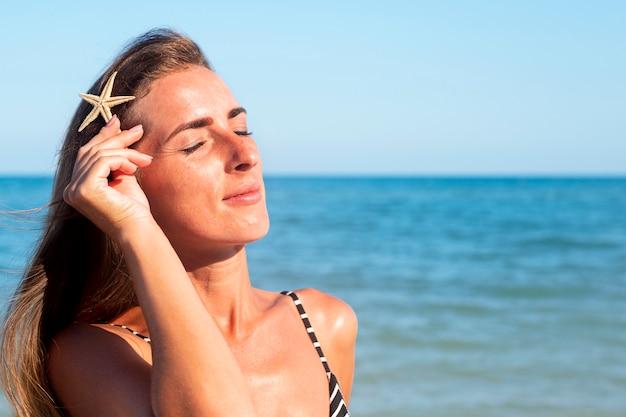 Jonge vrouw met gesloten ogen met een zeester op de achtergrond van de zee.