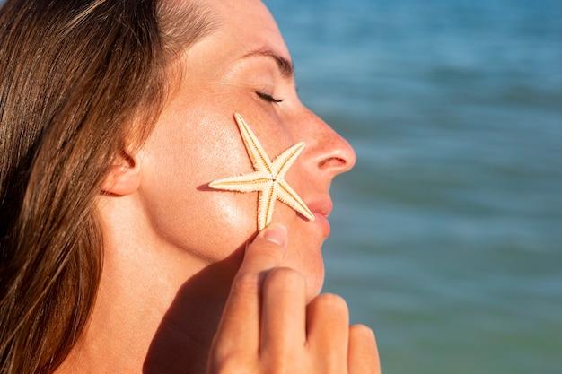 Jonge vrouw met gesloten ogen met een zeester op de wang tegen de zee.