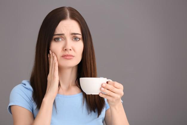 Jonge vrouw met gevoelige tanden en kop warme koffie op grijs