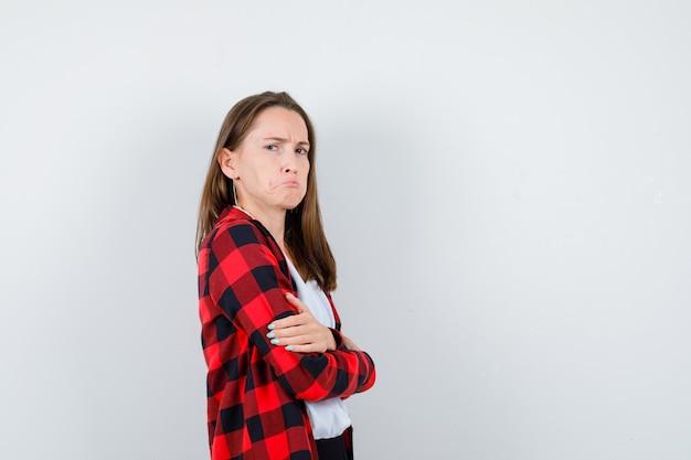 Jonge vrouw met gevouwen armen, gebogen onderlip in vrijetijdskleding en sulky kijkend.