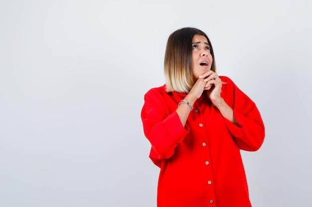 Jonge vrouw met gevouwen handen onder de kin in een rood oversized shirt en kijkt verbaasd, vooraanzicht.