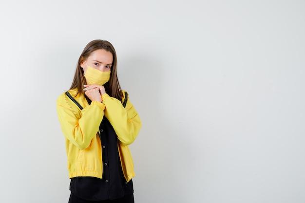Jonge vrouw met gevouwen handen onder kin