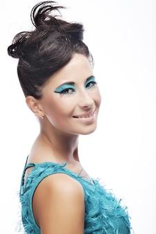 Jonge vrouw met geweldig kapsel in blauwe jurk