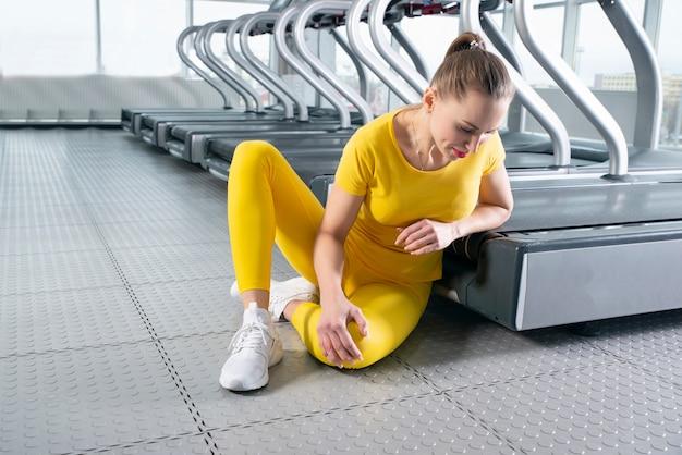 Jonge vrouw met gewonde knie zitten en pijn voelen