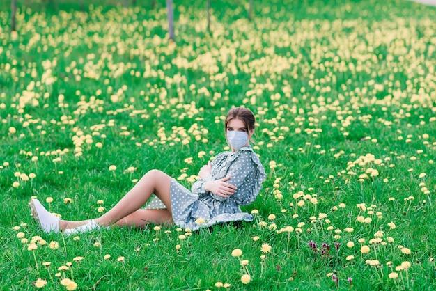 Jonge vrouw met gezichtsmasker buiten in een bloesemtuin. corona-virus concept.