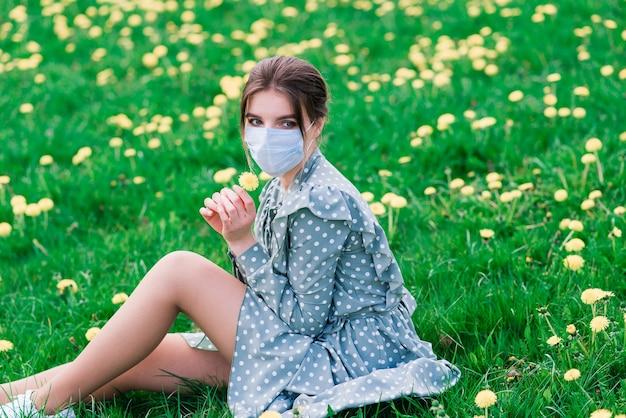 Jonge vrouw met gezichtsmasker buiten in een bloesemtuin. corona-virus concept. Premium Foto