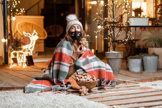 Jonge vrouw met gezichtsmasker die alleen nieuwjaarsvakantie viert, zittend met zoete peperkoeken op een terras thuis. concept van quarantaine en zelfisolatie tijdens de epidemie op feestdagen