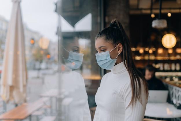 Jonge vrouw met gezichtsmasker die voor de ramen in café staat