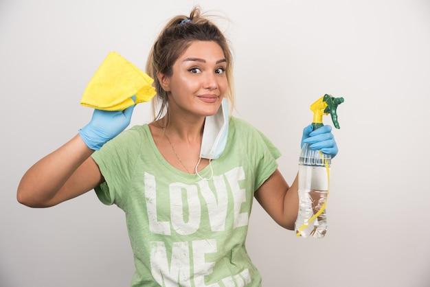 Jonge vrouw met gezichtsmasker en levert schoonmaakmiddelen op witte muur.