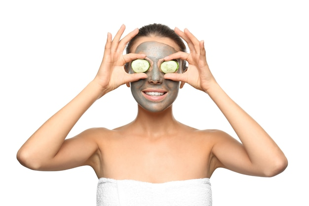 Jonge vrouw met gezichtsmasker en plakjes komkommer geïsoleerd