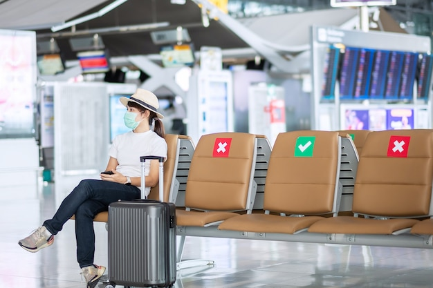 Jonge vrouw met gezichtsmasker en zittend op een stoel in de luchthaven, bescherming coronavirus (covid-19) infectie, aziatische vrouw reiziger. new normal, reisbel en sociaal afstand nemen