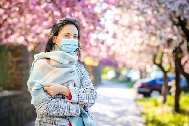 Jonge vrouw met gezichtsmasker in de lentestraat. covid-19-pandemie. corona-uitbraak.