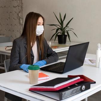 Jonge vrouw met gezichtsmasker op kantoor werken