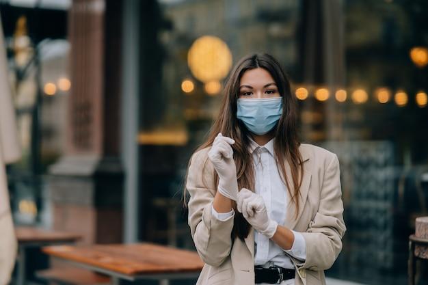 Jonge vrouw met gezichtsmasker op straat