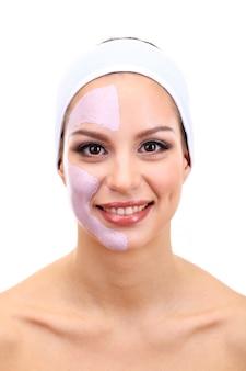 Jonge vrouw met gezichtsmasker van klei, geïsoleerd op wit