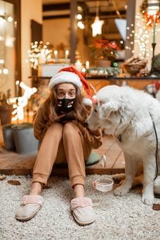 Jonge vrouw met gezichtsmasker vieren met een hond nieuwjaarsvakantie thuis. concept van quarantaine en zelfisolatie tijdens de epidemie op feestdagen