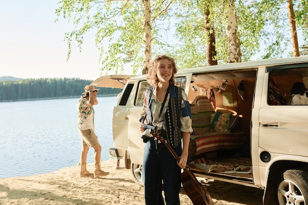 Jonge vrouw met gitaar die naar het uitzicht kijkt terwijl haar vrienden het kamp bij het meer regelen