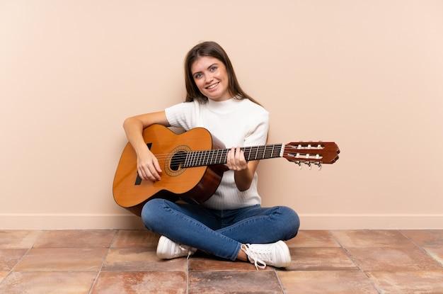 Jonge vrouw met gitaarzitting op de vloer